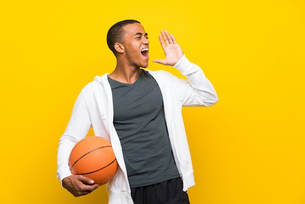 African american basketball player man shouting with mouth wide open
