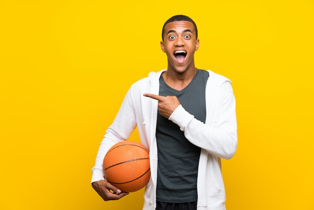 African american basketball player man surprised and pointing side