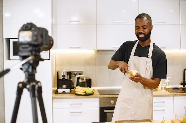 笑顔で料理をしているアフリカ系アメリカ人のひげを生やした男。自宅のキッチンでvlogを調理するためのブロガー撮影ビデオ。エプロンを着た男。