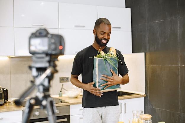 笑顔で食べ物のパッケージを持っているアフリカ系アメリカ人のひげを生やした男。自宅のキッチンでvlogを調理するためのブロガー撮影ビデオ。黒のtシャツを着ている少年。