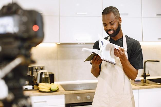 笑顔で料理本を読んでいるアフリカ系アメリカ人のひげを生やした男。自宅のキッチンでvlogを調理するためのブロガー撮影ビデオ。エプロンを着た男。