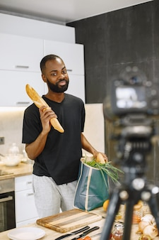 African-american bearded man smiling and holding a package with food. blogger shooting video for cooking vlog in kitchen at home. boy wearing black t-shirt.