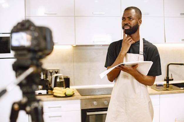 Uomo barbuto afroamericano che sorride e legge un libro di cucina. blogger gira video per cucinare vlog in cucina a casa