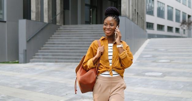 携帯電話で話し、外を歩いているアフリカ系アメリカ人の美しい幸せな笑顔の女性。携帯電話で話したり散歩したりする陽気な女性。電話での会話。
