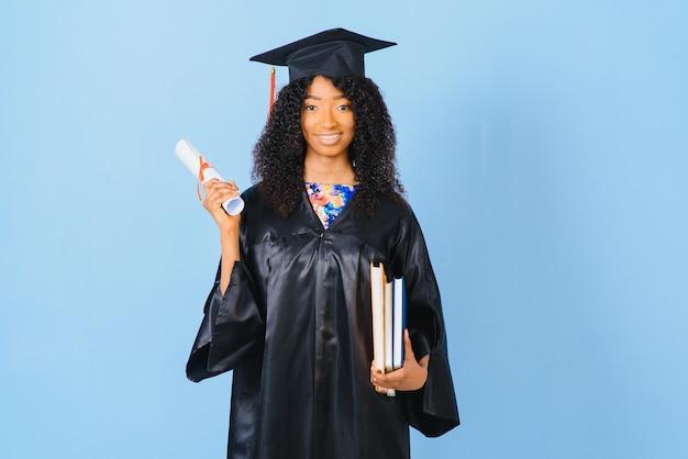 Афро-американская красивая женщина в черном халате и шляпе, на синем изолированном фоне улыбается.