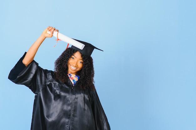 青い孤立した背景の笑顔で、黒いローブと帽子のアフリカ系アメリカ人の美しい女性。