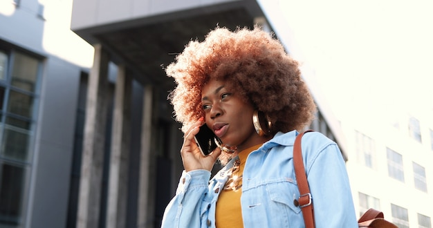 外の携帯電話で話しているアフリカ系アメリカ人の美しい女性。携帯電話で話すスタイリッシュな魅力的な女性。電話での会話。