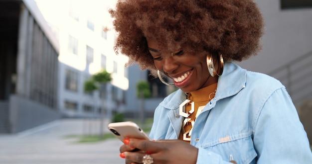 携帯電話をタップしてスクロールし、屋外で笑っているアフリカ系アメリカ人の美しい女性。スマートフォンでスタイリッシュな魅力的な女性のメッセージング。電話ソーシャルメディアチャット。