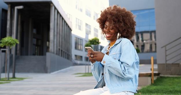 携帯電話をタップしてスクロールし、外のベンチに座っているアフリカ系アメリカ人の美しい女性。スマートフォンでスタイリッシュな魅力的な女性のメッセージング。電話チャット。