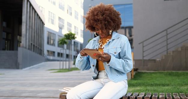 Афро-американская красивая женщина, нажимая и прокручивая на планшетном устройстве, улыбаясь и сидя на скамейке снаружи. стильные привлекательные женские сообщения и беседы на гаджетном компьютере в городе.