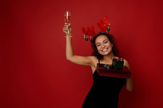 사슴뿔 고리와 검은 벨벳 드레스를 입은 아프리카계 미국인 아름다운 여성은 반짝이는 빨간색 녹색 종이로 포장된 선물 상자를 들고 스파클링 와인이 든 피리로 손을 듭니다. 크리스마스 컨셉