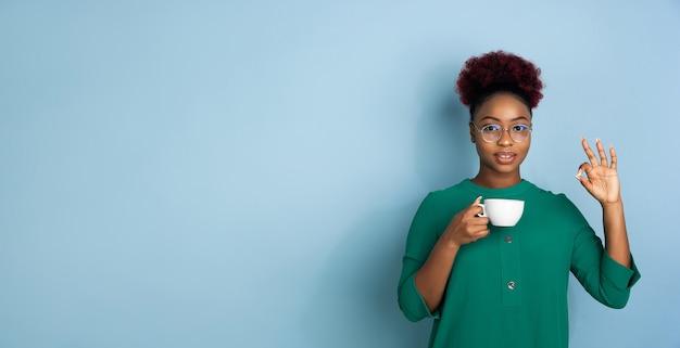 Портрет афро-американской красивой молодой женщины на синем фоне студии, эмоционально выразительный.
