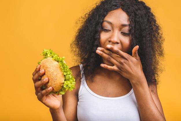 Афро-американский черный красивая молодая женщина ест гамбургер