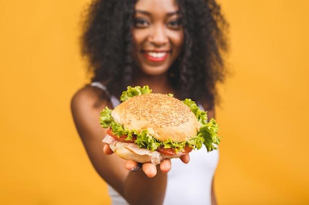 ハンバーガーを食べてアフリカ系アメリカ人の黒の美しい若い女性