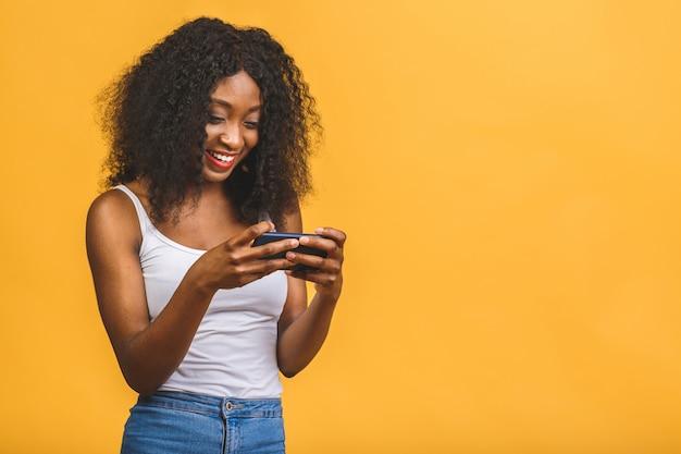 アフリカ系アメリカ人の黒人の女の子がwebでチャットの手電話で保持
