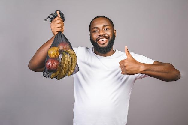 アフリカ系アメリカ人の黒人男性は、灰色の背景に分離されたプラスチックパッケージのない製品でメッシュバッグを保持しています。いいぞ。