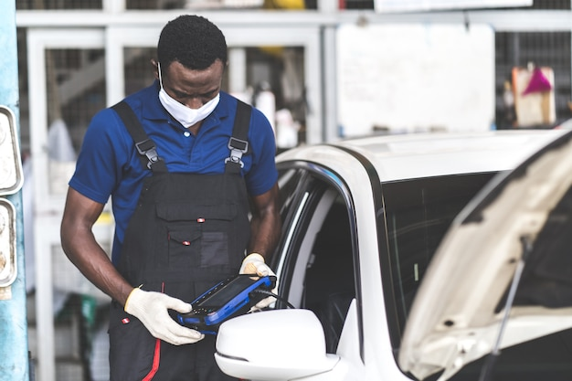 African american black people. professional car mechanic repair service and checking car engine by diagnostics software computer.