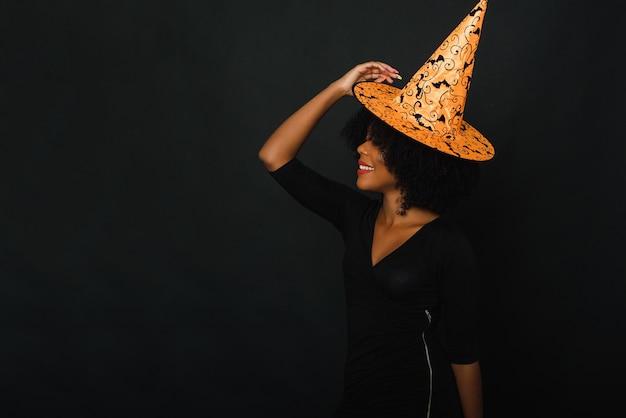 黒の背景にスタジオでハロウィーンの衣装でアフリカ系アメリカ人の黒人女性