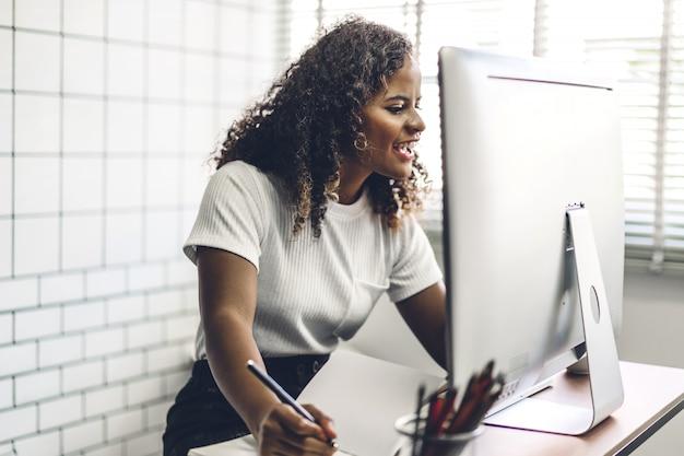 Афро-американская чернокожая женщина работая с портативным компьютером. творческие деловые люди, планирующие и использующие ручку в современном рабочем помещении