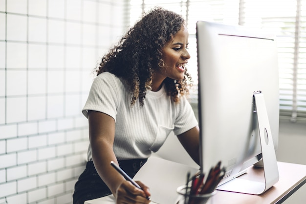 African american black woman working with laptop computer. creative business people planning and using pen in modern work loft