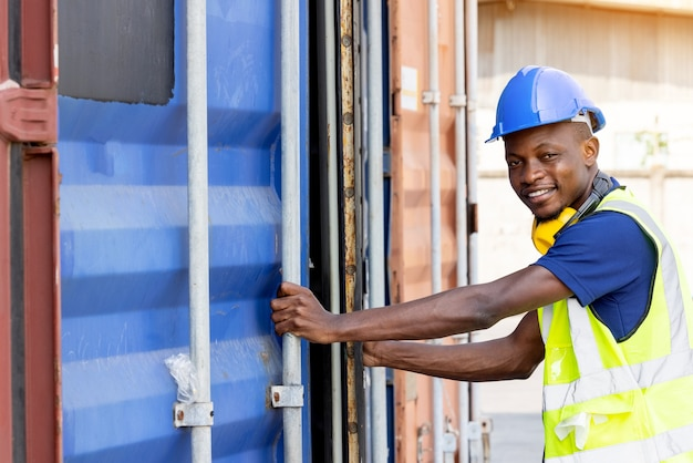 アフリカ系アメリカ人の黒人労働者が検査のためにコンテナを開けており、コンテナの修理が完了したことを確認しています