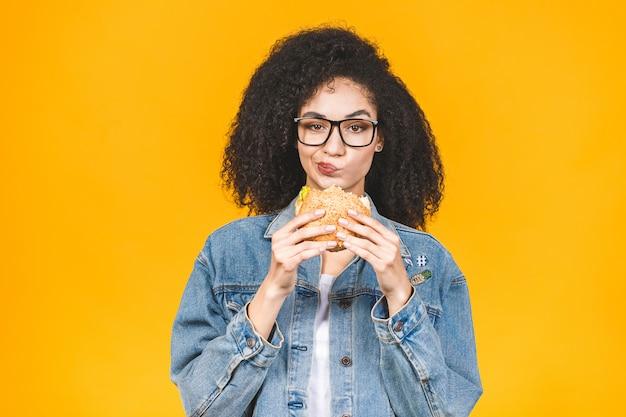 黄色の背景に分離されたハンバーガーを食べてアフリカ系アメリカ人の黒人の若い女性。