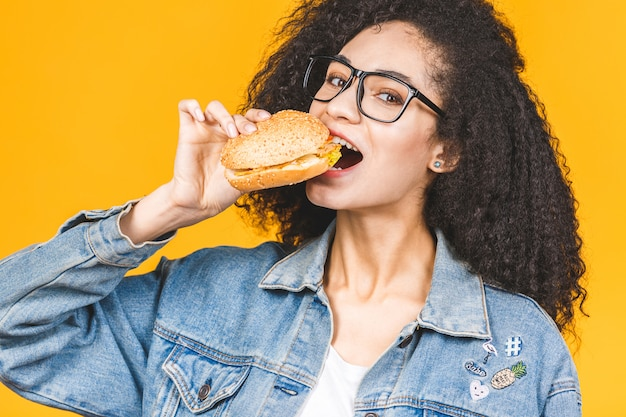 African american black young woman eating hamburger isolated on yellow background.