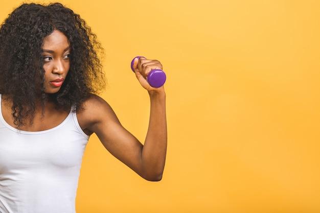 Афро-американская темнокожая молодая женщина тренирует мышцы с гантелями