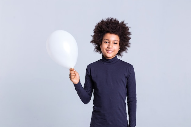 African american boy. beaming little boy standing on monochromic background and carrying white air balloon in one hand