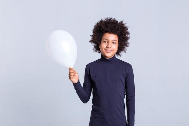 アフリカ系アメリカ人の少年。単色の背景に立って、片手に白い気球を運ぶ小さな男の子をビーム
