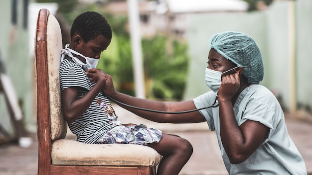 African-american boy getting a checkup by a doctor