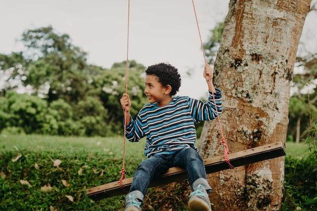 Афро-американский мальчик качается на качелях на природе
