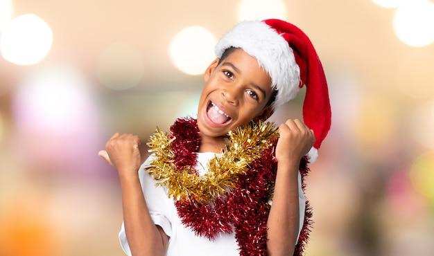 ぼやけた壁の上の勝利を祝うクリスマス帽子のアフリカ系アメリカ人の少年