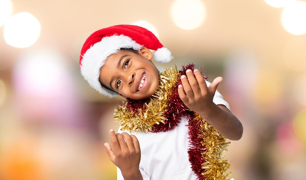 African american boy with christmas hat inviting to come with hand. happy that you came over blurred wall