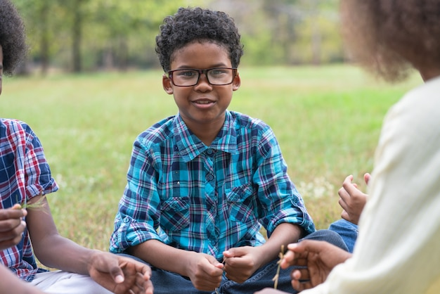 African american boy with friends sitting on the grass in the park