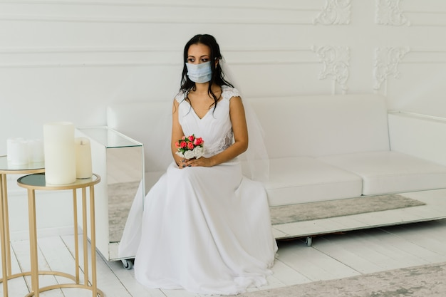 African american bride in dress, mask and in the morning preparing for the wedding in hotel room
