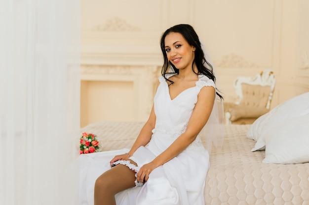 호텔 방에서 결혼식을 준비하는 아침에 드레스를 입은 아프리카계 미국인 신부
