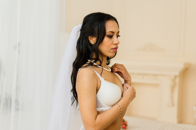 The african american bride in lingerie and veil preparing for the wedding in a hotel room