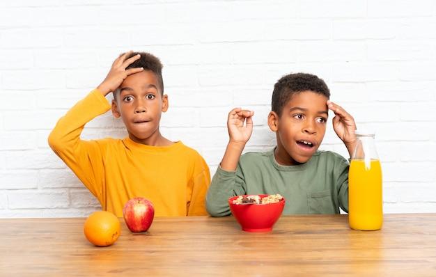 アフリカ系アメリカ人の兄弟の朝食と驚きのジェスチャーを行う