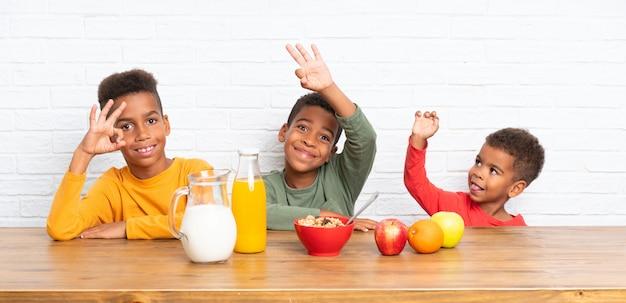 アフリカ系アメリカ人の兄弟が朝食を食べて、okサインを作る