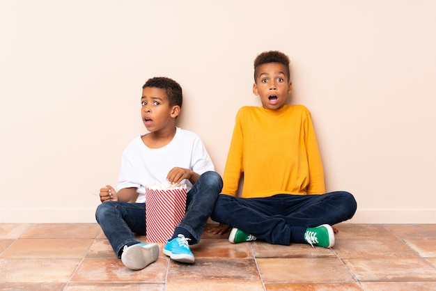 African american brothers  holding popcorns and doing surprise gesture