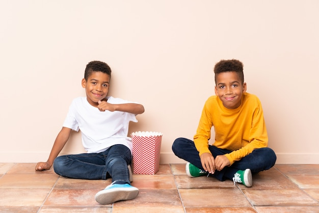 African american brothers  holding popcorns