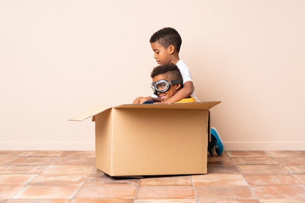 African american brothers playing, boy inside a cardboard box with aviator glasses