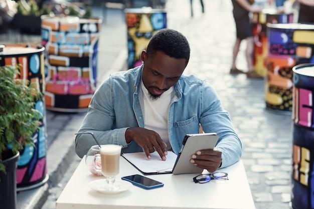 アフリカ系アメリカ人のビジネスマンが紙の文書を分析し、ブラジルの屋外カフェに座っているラップトップで作業します。