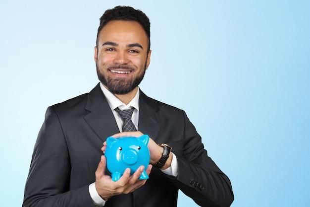 African american business man holding a piggy bank