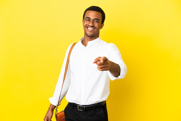 African american business man over isolated yellow background pointing front with happy expression