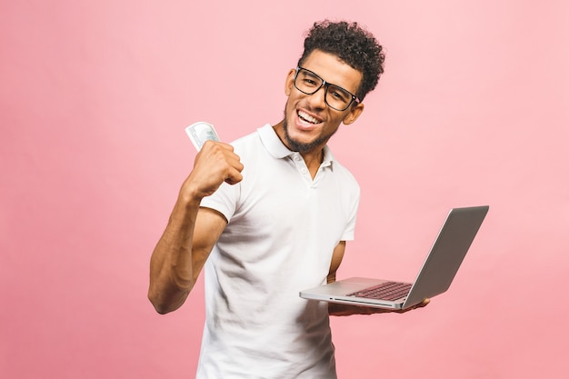 African american business man making money from internet, holding cash in hand and laptop in another
