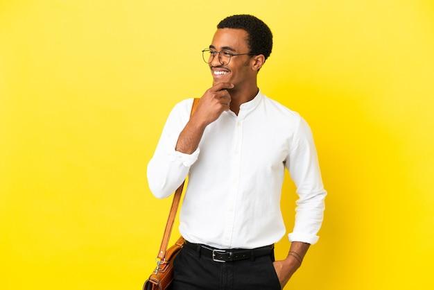 Афро-американский деловой человек на изолированном желтом фоне смотрит в сторону и улыбается