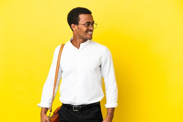 외진 노란색 배경 위에 있는 아프리카계 미국인 사업가가 옆을 바라보며 웃고 있다