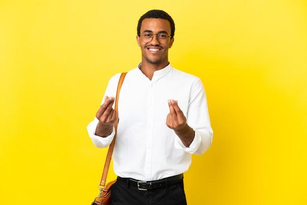 Афро-американский деловой человек на изолированном желтом фоне, делая денежный жест